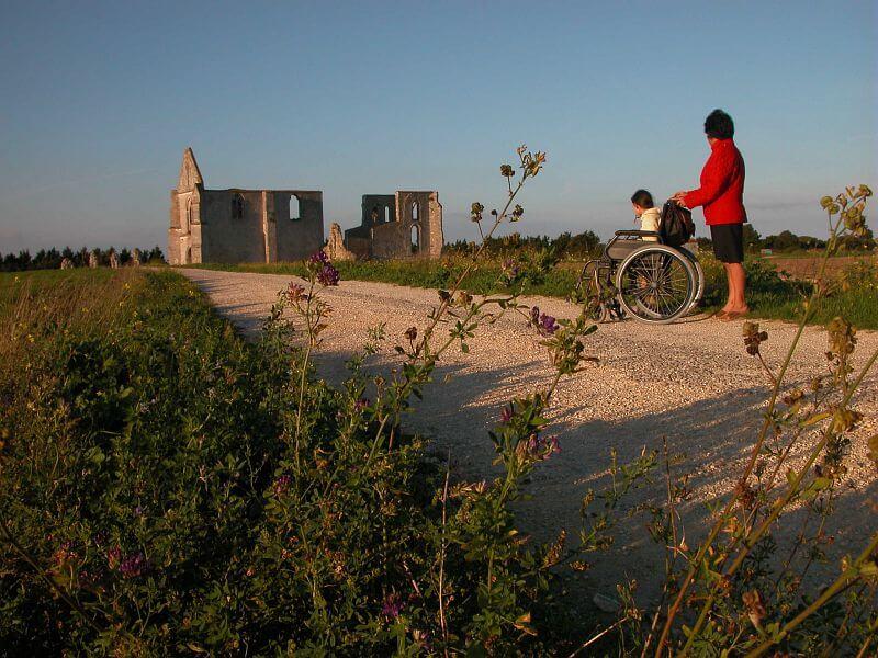 enfant en fauteuil roulant accompagné d'une personne valide visitant l'abbaye de chateliers à la flotte en ré