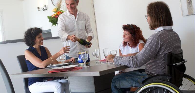 Personnes valides partageant un repas avec des personnes en situation de handicap, aveugle et en fauteuil roulant