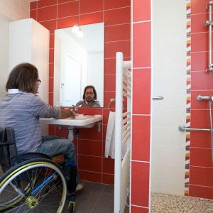 handicapé en fauteuil roulant prés d'un lavabo